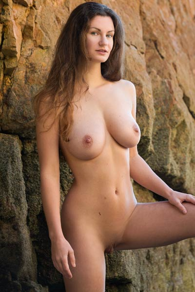 Graceful dame poses naked on the rocks and presents her massive melon shaped breasts