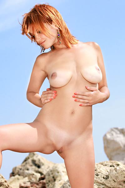 Enjoy the sunshine on the rocks with cute all natural redhead babe
