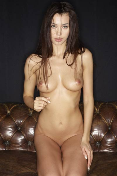 Fantastic brunette Nicolette poses naked on the leather sofa and presents her luscious body