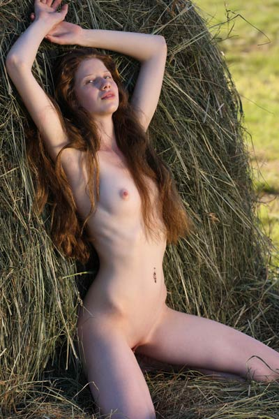 Skinny village girl posing butt naked outdoors by the haystack