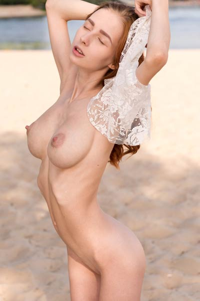 Skinny redhead bares her large perfectly shaped natural boobs for an outdoor photo shoot