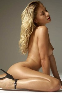 Curly blonde bombshell poses completely naked and teases with her perfect shiny body