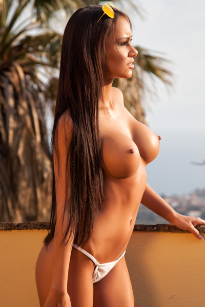 Sultry brunette vixen poses naked on the balcony teasing with her delectable curvy body