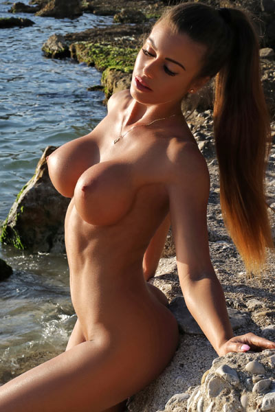 Well stacked babe seductively poses at the beach flaunting her irresistible busty body