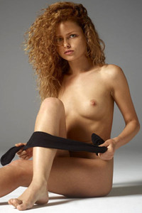 Curly bombshell Julia takes off her stockings seductively and shows off her gorgeous body