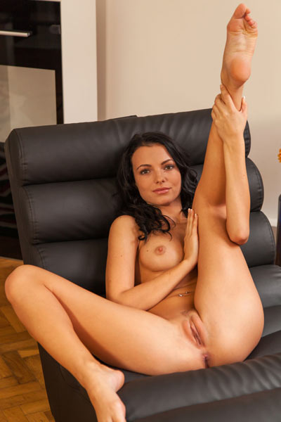 Gorgeous brunette with amazing smile gets naked on the leather sofa