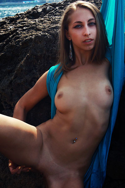 Posing naked on the rocks makes this all natural brunette chick hot and horny