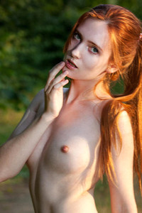 Redhead babe with small boobs posing all naked outdoors in nature