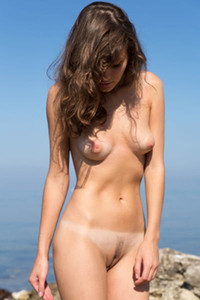 Absolutely gorgeous Carmela poses naked on the rocks baring her tanned body