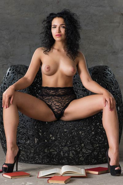 Dazzling curly babe poses in sexy black lingerie enhancing her amazing big boobs