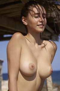 Beautiful Alisa displays her perfect pair of natural boobs while relaxing on the beach