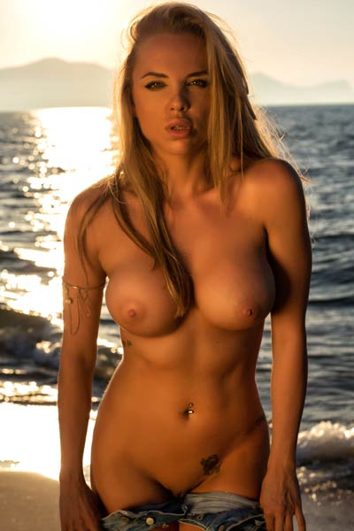 Fabulous blonde babe with huge tits presents her fascinating body at the beach