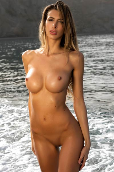 Top class babe poses naked on the beach baring her amazing tight body