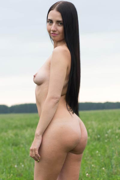 Sexy Veronica Snezna strips off her colorful dress outdoors on a meadow