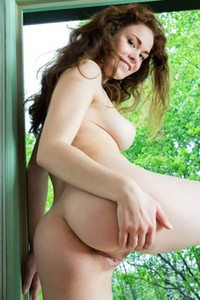 Cute pale skinned vixen shows her delicious pair of natural tits while doing a naked photo shoot