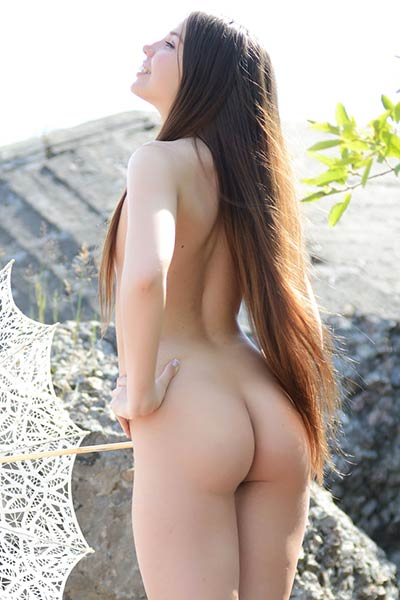 She is all natural brunette that likes to pose naked in nature