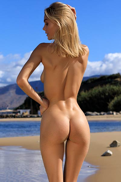 Lovely blonde vixen showcases her perfect naked body while having fun at the beach