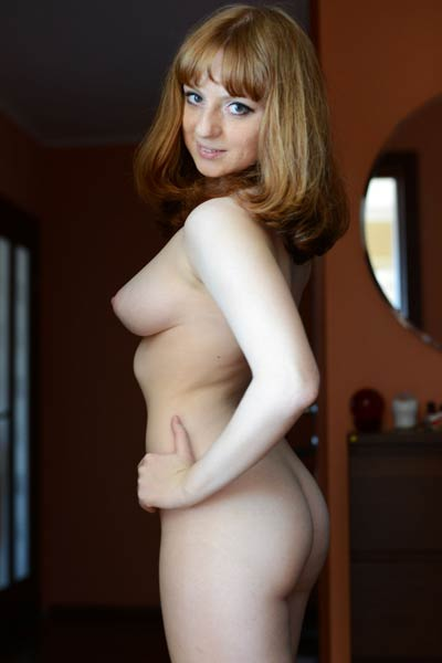 Sweet redhead Kataly strips her clothes and gives us a glint of her love holes