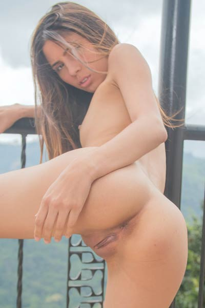 Young and sweet Latina Mily Mendoza poses naked on the balcony baring her smooth body and hot pussy