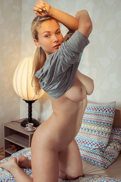 Seductive blonde chick Caroline Abel slowly strips naked and dazzles us with her amazing puffy tits