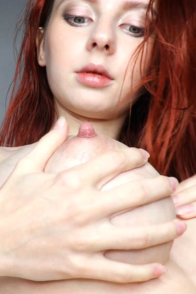 Foxy redhead vixen seductively strips naked and squeezes her big boobs for you