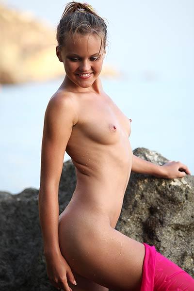 Blonde model April having fun in nude on the rocks on the seashore