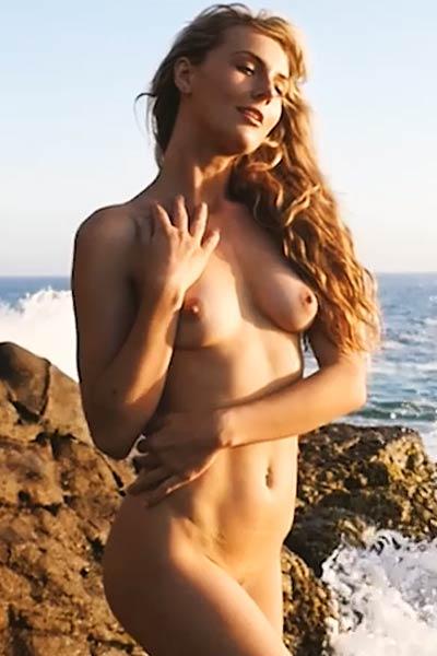 Adventurous and beautiful babe striptease performance at seashore