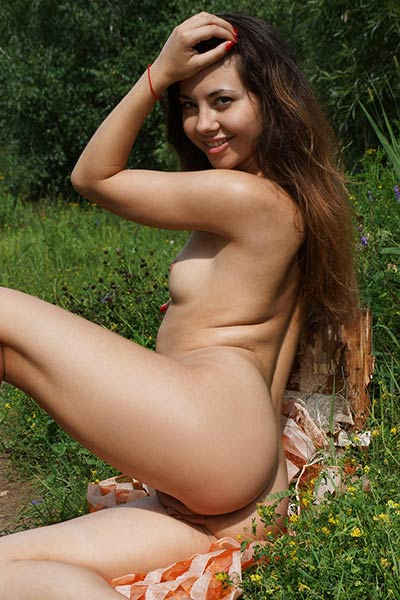 Sexy brunette with gorgeous smile is outdoors in nature showcasing her sexy curves