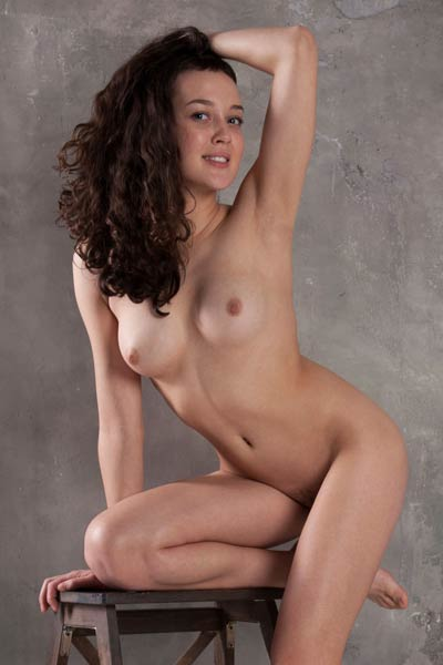 All naked and all natural brunette model teasing in many different poses on the chair