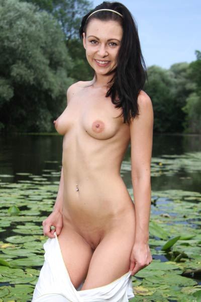 Sexy and hot brunette is in shallow water stripping and posing