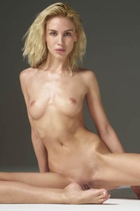 Flexible and charming blonde Marika shows her shaved pussy posing seductively