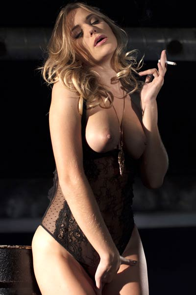 A confident busty blonde smokes her cigarette and shows off her body in burning hot poses