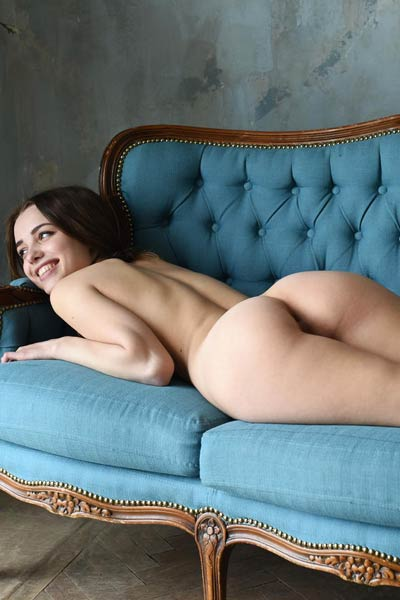 Beautiful Saloma is at home on her blue sofa stripping and posing in nude