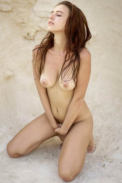 Brunette goddess Alisa poses naked in the sand and shows off her delightful body