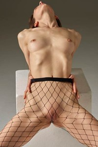 Charming young lady Flora poses naked wearing only fishnets