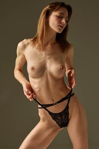 Elegant brunette seductively strips her black lingerie and presents her slender body