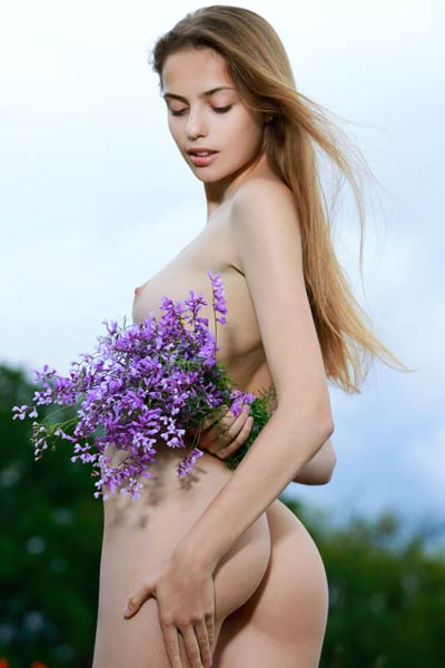 Fabulous beauty strips naked in a flowery field and shows off her magnificent ass and pussy