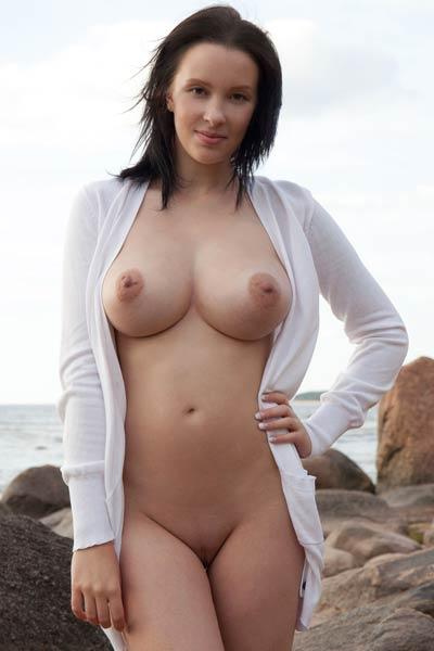 Chick with big rounded melons posing naked on the rocks