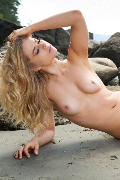 Maya Rae is alone on the beach stripping and posing