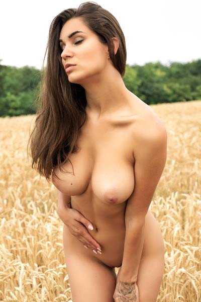 Hot tanned brunette gets nude outdoor showing off her well endowed body and awesome boobs