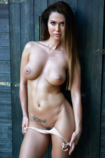 A flirty and playful brunette poses naked by the wood barn showing off her attributes