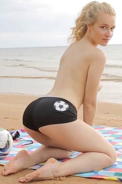 Sensual blonde goes wild getting naked and posing on the seaside