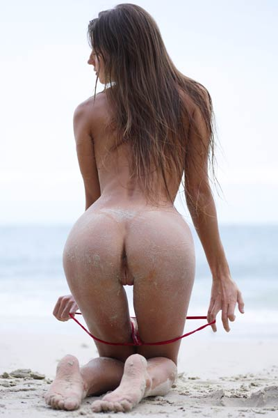 Sultry Angel Melena Maria crawls naked on the beach with her amazing ass covered with sand
