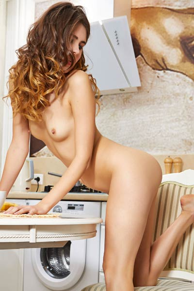 Sweet curly babe playfully poses in the kitchen showing off her seductive body