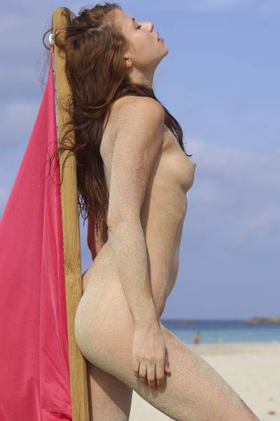Gorgeous brunette doll Jenna playfully poses on the beach showing off her hot sanded body