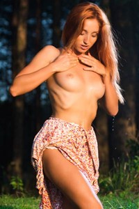 Nicely curved chick is outdoors in the woods posing all naked