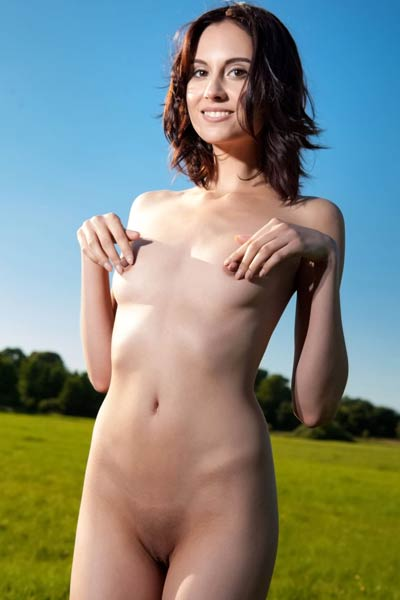 All natural doll Sabrina G playfully poses in the meadow showing off her slender body