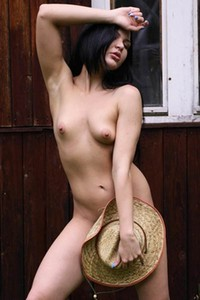 Dark haired vixen Oxana C poses naked by the barn and teases with her hotness