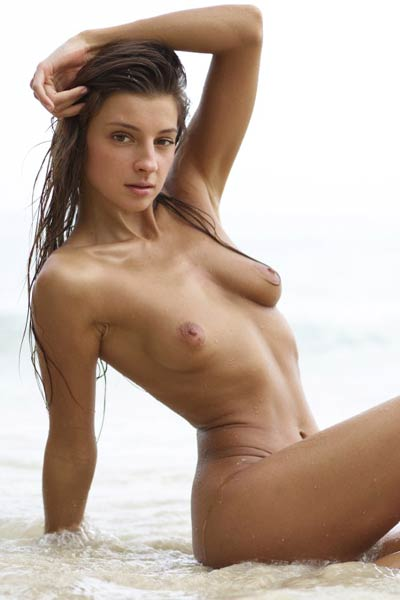 Magnificent Melena Maria poses naked on the beach baring her tanned and smooth slender body