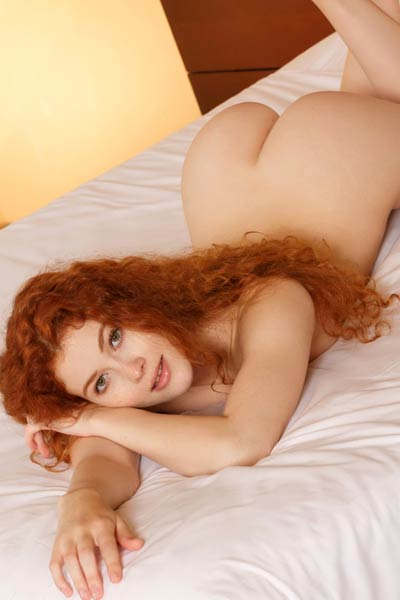 Redhead Adel C rolling onto her back with her legs wide open showing her little pussy